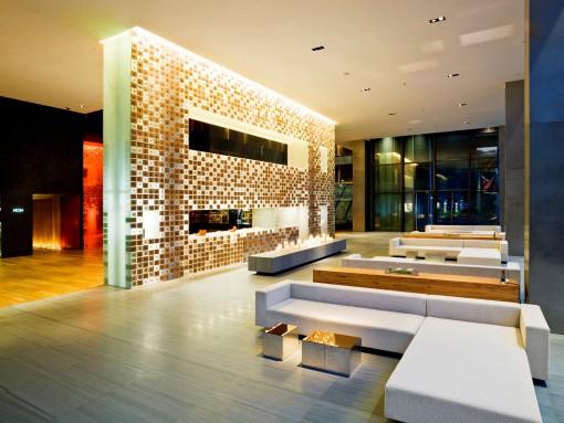 Lo spazio d'ingresso con l'illuminazione serale. In evidenza la parete espositiva retroilluminata realizzata con pannelli in acrilico e legno di olmo