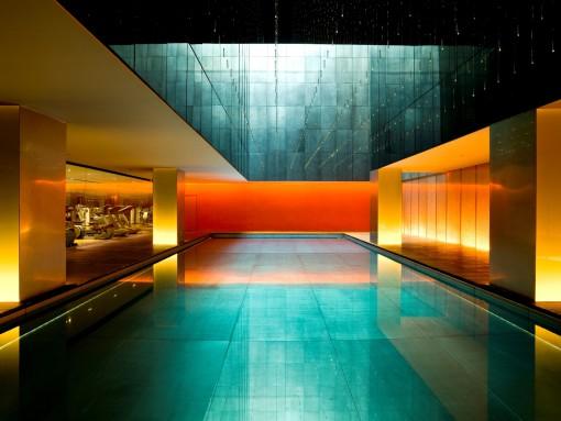 Un'altra immagine della grande piscina, illuminazione serale. L'effetto combinato di un'illuminazione puntiforme con fibre ottiche, luce naturale e di un' illuminazione architettonica con sistemi a scomparsa