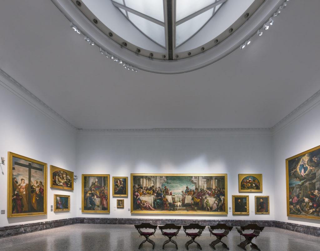 """Pinacoteca di Brera, Sale Napoleoniche – sala VIII. Sullo sfondo, il grande telero di Gentile e Giovanni Bellini (""""La Predica di San Marco ad Alessandria d'Egitto"""", 1504-1507 (cortesia:ERCO)"""