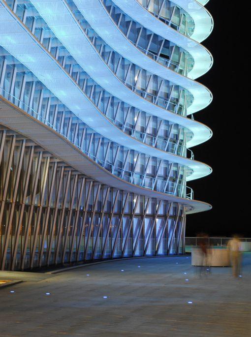 Zaragoza, Torre del Agua. Le strutture orizzontali della facciata sostengono gli apparecchi di illuminazione, che forniscono l'illuminazione diretta verso l'alto e restano invisibili, sia esternamente sia internamente, grazie al loro montaggio e orientamento. L'area circostante è illuminata dalla luce riflessa dalla torre. In questa zona, apparecchi a LED rotondi incassati creano punti di luce blu, che sono posizionati secondo gli schemi lineari della pavimentazione, e ricreano così le linee nella notte mediante sequenze di punti (cortesia: Artec3 Lighting Design Vision, Barcellona ) (cortesia foto: Xabier Graells, cortesia Lamp)