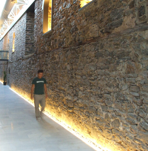 Uno dei passaggi corridoio interni: è visibile l'interazione fra luce naturale proveniente dai lucernari e luce artificiale (cortesia: Studio Paola Urbano)