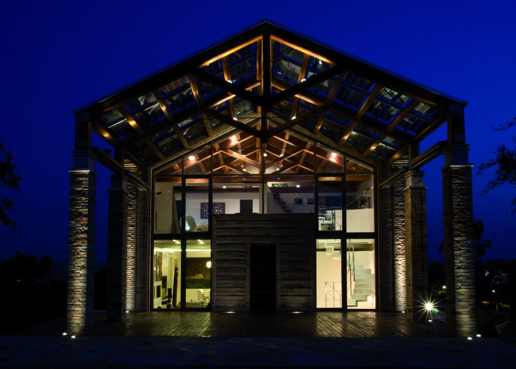 Un'immagine notturna della facciata principale dell'abitazione, con l'illuminazione interna degli ambienti (cortesia: A&EFFE Studio Architettura)