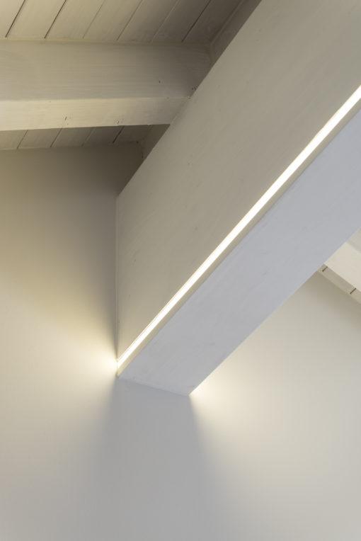 Sulla trave portante LED strip dimmerabili segnano le geometrie dello spazio come lame di luce