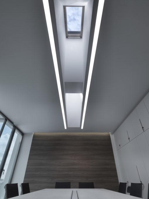 Un'immagine della sala riiunioni principale dovele linee luminose corrono parallele ai due lucernari del tetto (courtesy: Performance in Lighting)