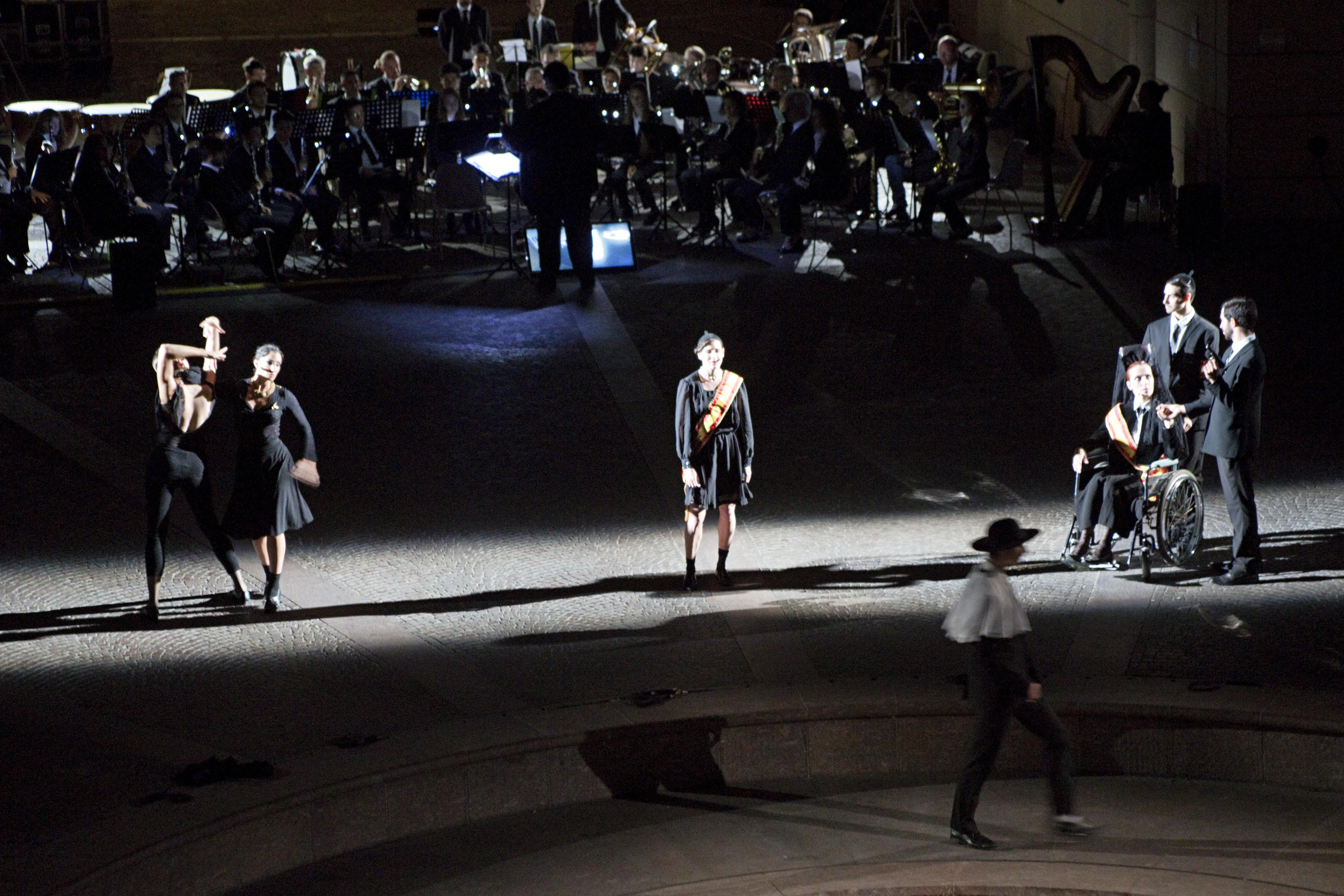 """Rovereto, """"Los Pajaros Muertos"""". Le figure centrali sono illuminate di taglio da entrambi i lati da quattro sagomatori che formano una strada di luce che percorre tutta la larghezza del palcoscenico, la figura in primo piano è illuminata debolmente da tre PC da tre direzioni diverse. L'orchestra ha un controluce di fresnel ed il maestro ha un piccolo taglio di luce blu. Tutti gli apparecchi di illuminazione hanno gelatine 201 Lee (courtesy photo: Sandra Raccanello)"""