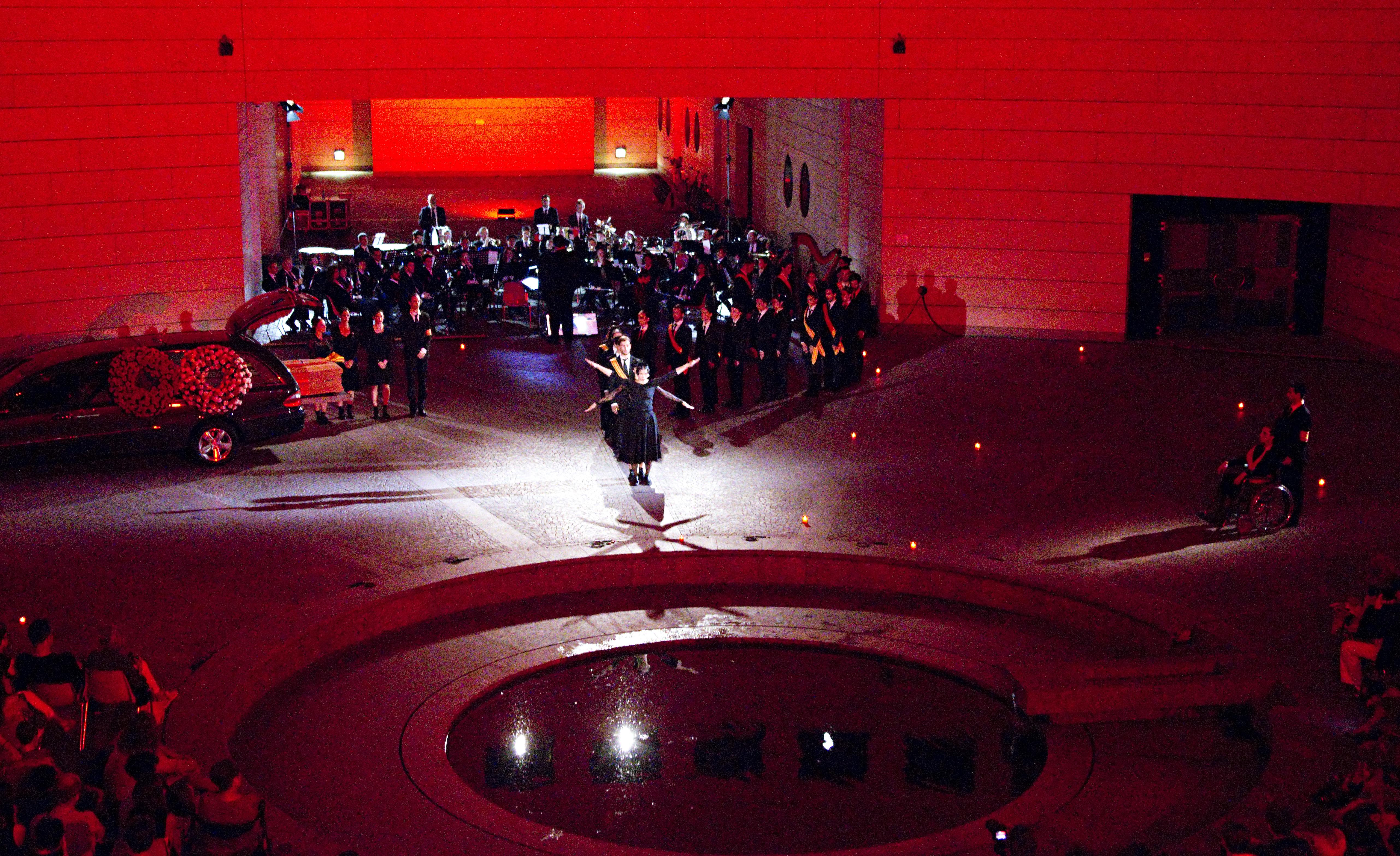 La parete è illuminata con apparecchi a LED per architettura di colore rosso, l'orchestra prende un controluce da alcuni Fresnel montati su cavalletto, mentre il gruppo centrale ha un controluce di quattro PAR concentrati al centro e un taglio di due PAR da destra. I personaggi a destra prendono un taglio di un PC da destra. Tutti gli apparecchi hanno gelatine 201 Lee (courtesy photo: Sandra Raccanello)